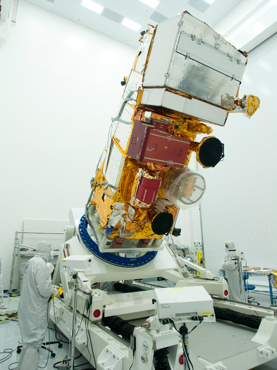 The NPP spacecraft in a cleanroom at Ball Aerospace undergoes inspection by a technician following electromagnetic compatibility testing. Credit: Ball Aerospace