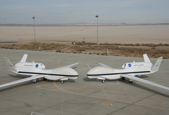 Their bulbous noses almost touching, NASA's two Global Hawks lined up nose-to-nose on the ramp at NASA's Dryden Flight Research Center on Edwards Air Force Base. Bearing NASA tail numbers 871 and 872, the two autonomously operated unmanned aircraft will be flown during the coming multi-year HS3 hurricane study. Credit: NASA / Tony Landis