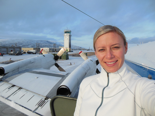 Christy Hansen in Kanger, Greenland, after one of Operation IceBridge's science flights. Behind her is the air traffic control tower, as well as the P-3B propellers. Credit: Christy Hansen