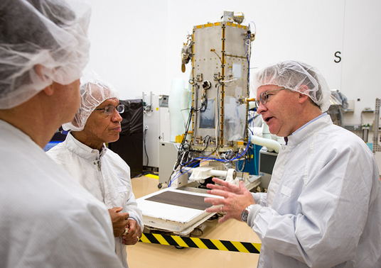 NASA Administrator Charles Bolden, left, listens as CEO and President of Orbital Sciences Corporation David Thompson, right, talks about the Orbiting Carbon Observatory 2 (OCO-2) satellite, background, in a clean room at Orbital's facility in Gilbert, AZ, on August 9, 2013. Credit: NASA/Bill Ingalls.