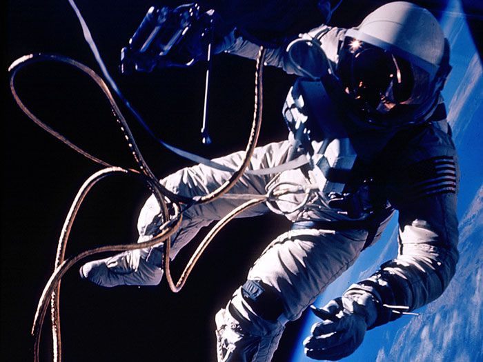 The United States' first spacewalk, made by Ed White on June 3, 1965 during the Gemini 4 mission. On the third orbit, White opened his hatch and used a hand-held manuevering oxygen-jet gun to push himself out of the capsule. After the first three minutes the fuel ran out and White manuevered by twisting his body and pulling on the tether. His extra-vehicular activity started over the Pacific Ocean near Hawaii and lasted 23 minutes, ending over the Gulf of Mexico. The photograph was taken by commander James McDivitt.