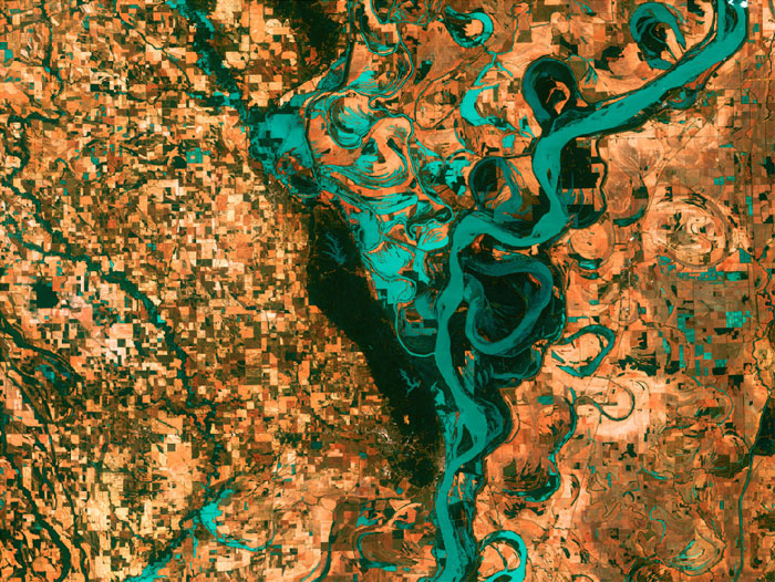MEANDERING MISSISSIPPI: Small, blocky shapes of towns, fields, and pastures surround the graceful swirls and whorls of the Mississippi River. Countless oxbow lakes and cutoffs accompany the meandering river south of Memphis, Tennessee, on the border between Arkansas and Mississippi, USA. The 'mighty Mississippi' is the largest river system in North America. Image taken by Landsat 7 on May 28, 2003.