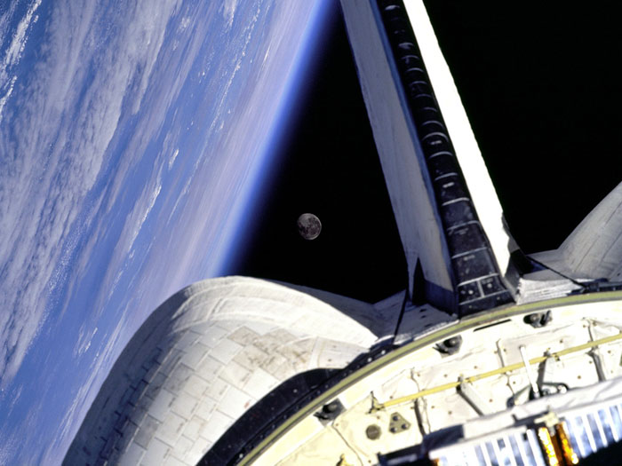 MOON FRAME: Earth and its Moon are nicely framed in this image taken from the aft windows of the Space Shuttle Discovery in 1998. Discovery, on mission STS-95, was flying over the Atlantic Ocean at the time this image was taken.