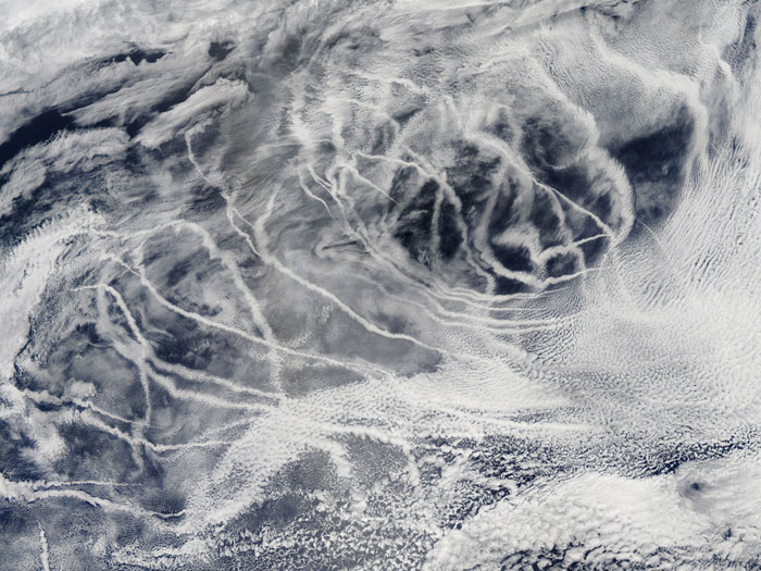 SHIP TRACKS: 'Ship tracks' above the northern Pacific Ocean. These patterns are produced when fine particles from ship exhaust float into a moist layer of atmosphere. The particles seed new clouds or attract water from existing cloud particles. Image taken by the Moderate Resolution Imaging Spectroradiometer (MODIS) onboard NASA's Aqua satellite on July 3, 2010.