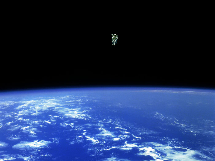 TO BOLDLY GO: February 12, 1984: Mission specialist Bruce McCandless II ventures further away from the confines and safety of his ship than any previous astronaut has ever been. This space first was made possible by the Manned Manuevering Unit or MMU, a nitrogen jet-propelled backpack. After a series of test maneuvers inside and above Challenger's payload bay, McCandless went 'free-flying' to a distance of 320 feet away from the Orbiter. This stunning orbital panorama view shows McCandless out there amongst the black and blue of Earth and space.