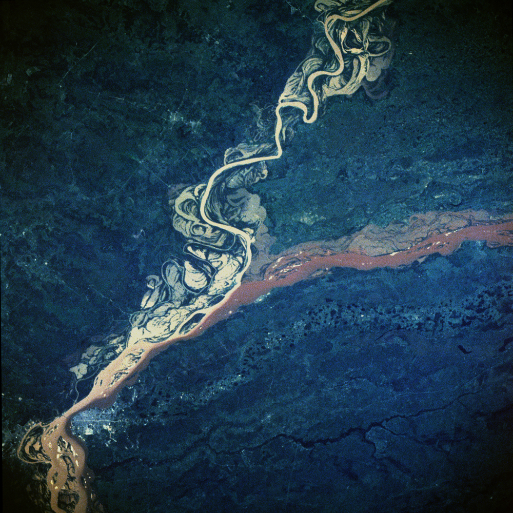 This image, taken in February 1984, shows the confluence of the Parana and Paraguay Rivers northeast of the town of Corrientes, in Argentina. The Parana is South America's second largest river (the Amazon being the largest), and the river and its tributaries are important transportation routes for landlocked cities in Argentina, Paraguay, Bolivia and Brazil. Both the Parana and Paraguay Rivers are loaded with sediment; the Paraguay (left) contains a tan sediment and the Parana (right) contains a reddish-brown muddy sediment. As the two rivers merge in the center of the photo and begin to flow southwest, we see how their sediments remain fairly unmixed for many miles downstream.